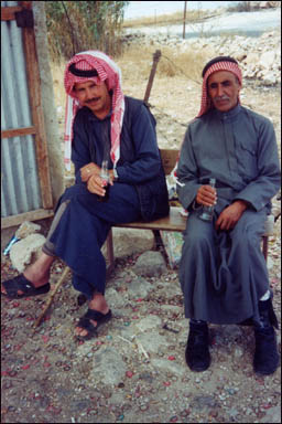 Two villagers enjoy a cold bottle of Coca-Cola outside a small shop. Near El-Greyat, Beni-Hamida Mountains, Jordan.